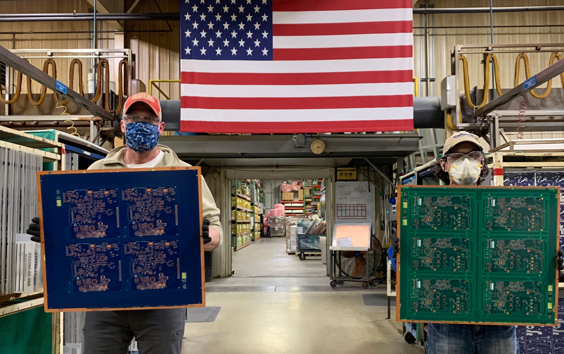 Calumet Electronics employees holding circuit boards created for breathing machines that help fight COVID-19